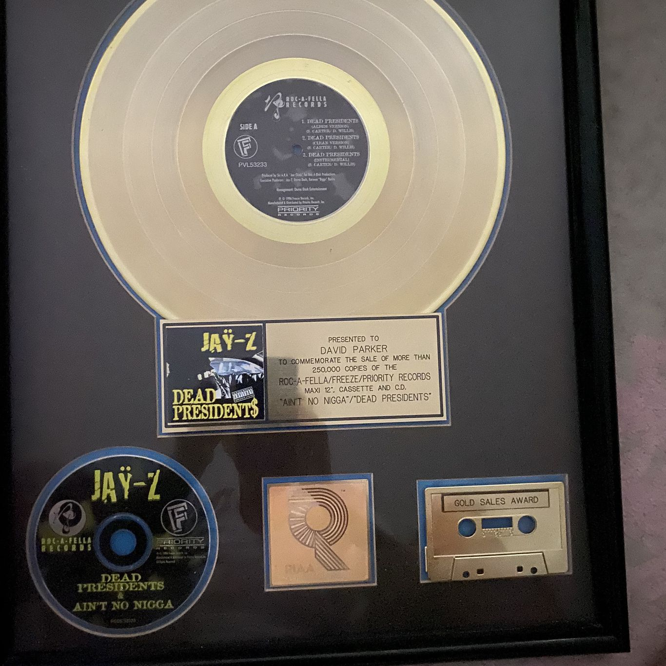 "A gold record for Jay-Z's ""Ain't No Nigga/Dead Presidents"" at the Amherst Records offices. For ""Ain't No Nigga,"" producer Big Jaz sampled The Whole Darn Family's ""Seven Minutes of Funk"""